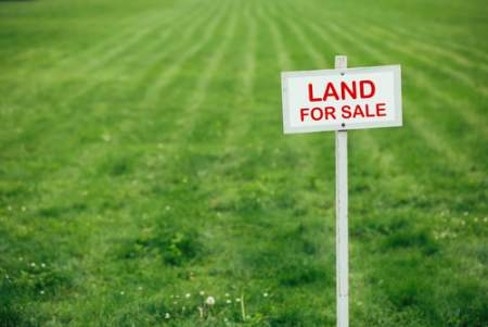 selling acreage with land for sale sign on green grass