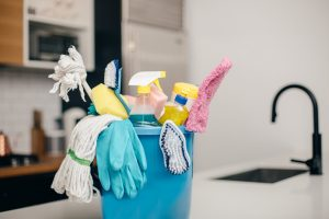 A bucket with cleaning supplies sitting on a counter