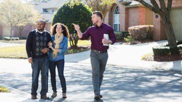 Man walking couple down a residential street